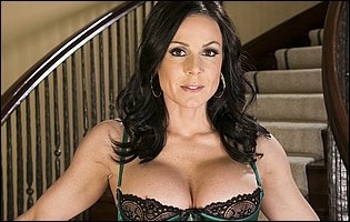 Gorgeous brunette Kendra Lust in sexy underwear, black stockings and high heels posing on stairs
